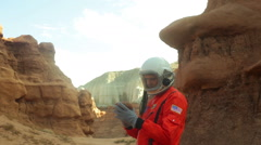 Astronaut looking at rock mars study Stock Footage