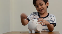 Little boy saving money in to piggy bank Stock Footage