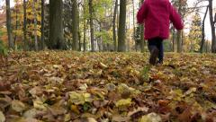Girl in a red coat running through the forest full of yellow autumn foliage Stock Footage