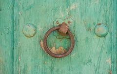 Front view of old doorknocker and green painted wooden door - stock photo
