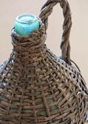 Glass bottle antique wicker-clad to hold wine and oil Stock Photos
