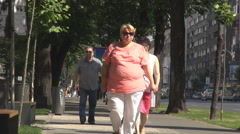 Fat woman walking on crowded street, pedestrians move downtown in green alley Stock Footage