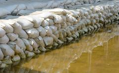 white sandbags for flood defense and it's reflection brown water - stock photo