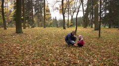 Dad and daughter to study nature on the leaves in the park Stock Footage