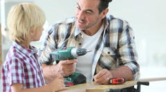 Man with little boy using electric drill Stock Footage