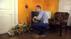 Man handles wood in pile near old stove in living rural room Stock Footage