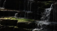 Small waterfall, gentle flowing water over moss covered rocks, dappled sun - stock footage