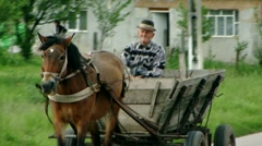 Man in Carriage pulled by Horse through a small Village Stock Footage