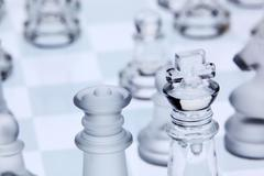 Chess pieces on a glass chess board Stock Photos
