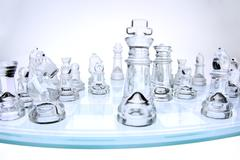 chess pieces on a glass chess board - stock photo