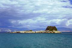 Rocky island in the ionian sea and the mountains Stock Photos