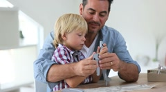 Father and kid making a plane model Stock Footage