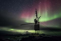 Automated remote weather station in the Arctic - Northern Lights - stock photo