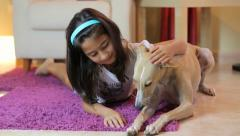 Happy Little Girl Petting Her Dog At Home Stock Footage