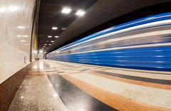 blue subway train in motion at the station - stock photo