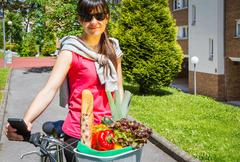 Young sportive woman with groceries in a basket bike - stock photo