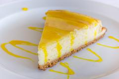 Lemon cheese cake with sauce on a white plate Stock Photos