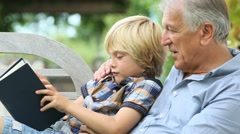 Grandfather reading book with grandson Stock Footage