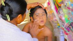 Bagan, myanmar - circa jan 2014: mother applies sunscreen thanaka on her daug Stock Footage