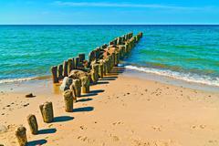 Beautiful beach, sea and breakwater - stock photo