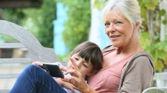 Senior woman with grandkid playing game on smartphone Stock Footage