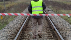 Railway employee behind warning tape on the railway Stock Footage