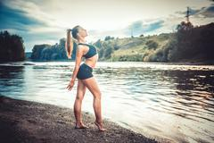 Athlete engaged in the sunset by the river - stock photo