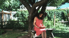Woman under a tree reading Stock Footage