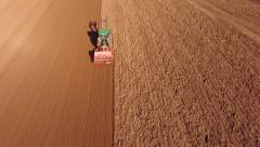 Aerial view of a farmer sowing wheat on a huge field with his tractor. Stock Footage