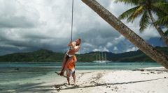 Couple swinging on the beach Stock Footage