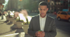 Young African American black Latino man in city texting smart phone cellphone 4k - stock footage