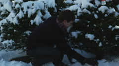 Young couple having a snowball fight in a grove of pine trees Stock Footage
