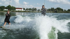 Two people wakeboarding behind a boat Stock Footage