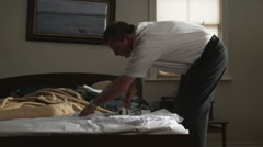 man trying to iron clothing on a bed - stock footage