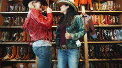 Two women trying on leather jackets and cowboy hats at a western store Stock Footage