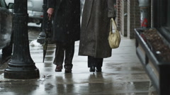 Senior couple walking down a snowy street and kissing Stock Footage