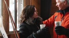 Mature couple drinking coffee and talking and laughing in the lodge of a ski Stock Footage