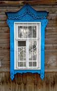Blue window in traditional tribal Russian style on facade of ancient wooden slum Stock Photos