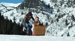 Dad pushing his wife and daughter on a toboggan Stock Footage