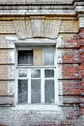 Stock Photo of Old window in aged slum house in Russia