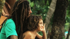 Father and son with dreadlocks sitting beneath palm trees Stock Footage