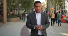 Young African American black Latino man in city walking texting smart phone 4k - stock footage