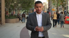 Young African American black Latino man in city walking texting cellphone - stock footage