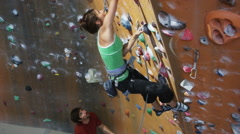 Woman on an indoor climbing wall as a man belays below Stock Footage