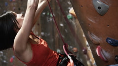 Woman on an indoor climbing wall Stock Footage