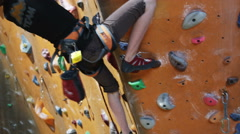 Girl on an indoor climbing wall Stock Footage