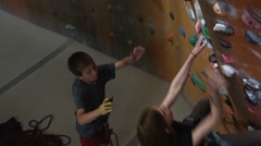 Girl on an indoor climbing wall with a boy belaying below Stock Footage