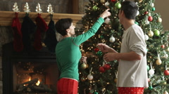 Mid adult couple decorating a Christmas tree with ornaments Stock Footage