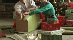 Mid adult couple wrapping Christmas presents Stock Footage