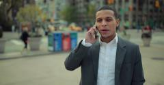 Young African American black Latino man in city walking talking on cellphone 4k - stock footage